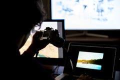 Jeune photographe masculin éditant le studio fait de photos à la maison sur l'ordinateur portable et l'ordinateur de bureau f image stock