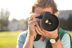 Jeune photographe masculin prenant la photo avec l'appareil-photo professionnel sur la rue photo stock