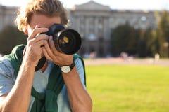Jeune photographe masculin prenant la photo avec l'appareil-photo professionnel sur la rue photographie stock libre de droits