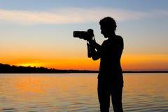 Jeune photographe masculin prenant la photo du coucher du soleil de rive avec l'appareil-photo professionnel photo libre de droits