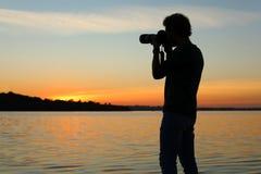 Jeune photographe masculin prenant la photo du coucher du soleil de rive avec l'appareil-photo professionnel images libres de droits