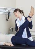 Jeune physiothérapeute Assisting Senior Woman avec l'exercice de jambe Images stock