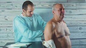 Jeune physiothérapeute travaillant avec le patient supérieur dans la clinique Examen du bras endolori banque de vidéos