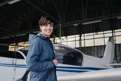 Jeune pilote de sourire posant avec un avion de propulseur Photographie stock libre de droits