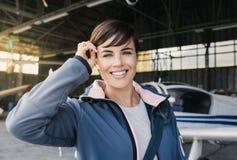 Jeune pilote de sourire posant avec un avion de propulseur Photo stock