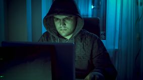 Jeune pirate informatique dans le hoodie travaillant sur l'ordinateur la nuit Image stock