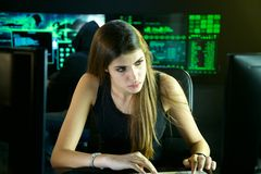 Jeune pirate informatique féminin étudiant le code avec l'associé - dans - crime images stock