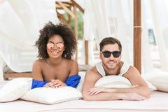 Jeune plaisir gai de sentiment de couples se reposant sur la plage Photos libres de droits