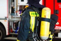 Jeune pompier dans l'uniforme devant le firetruck image stock