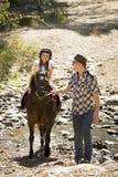 Jeune poney d'équitation d'enfant de jockey dehors heureux avec le rôle de père comme instructeur de cheval dans le regard de cow Images stock