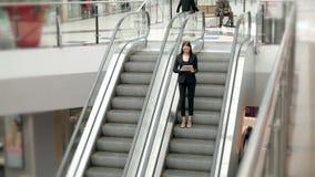 Jeune portrait de femme d'affaires parlant au téléphone sur des escalators Femme d'affaires intégrale dans le centre commercial o Photographie stock