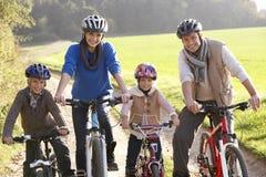 Jeune pose de famille avec des vélos en stationnement Image libre de droits