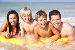 Jeune pose de famille sur la plage Photographie stock libre de droits