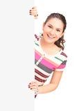 Jeune pose femelle de sourire sur un panneau vide Photographie stock libre de droits