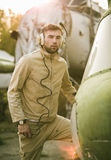 Jeune pose pilote près de l'hélicoptère Photographie stock libre de droits