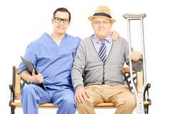 Jeune pose professionnelle masculine avec le monsieur plus âgé assis dessus Images libres de droits