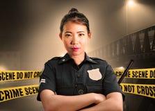Jeune position américaine asiatique de policier sérieuse dans la garde de la scène du crime pour préserver des preuves à pour fai image libre de droits
