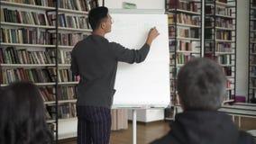 Jeune position asiatique d'homme avec un flipchart pendant sa conférence banque de vidéos