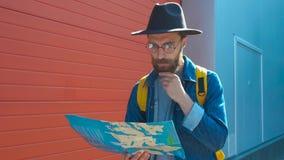 Jeune position attrayante d'homme et regarder une carte dans la rue au soleil banque de vidéos