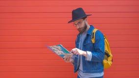 Jeune position attrayante d'homme et regarder une carte dans la rue au soleil clips vidéos