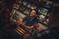 Jeune position de barman au compteur de barre avec des visiteurs buvant des cocktails ayant la conversation gentille images libres de droits