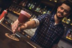 Jeune position de barman au plan rapproché de cocktail de portion de compteur de barre gai photos libres de droits