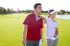 Jeune position de couples de joueurs de terrain de golf Photo stock