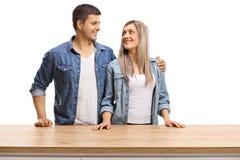Jeune position de couples derri?re un compteur en bois et regarder l'un l'autre photographie stock