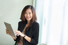 Jeune position de femme d'affaires tandis que regard à un PC de comprimé Photographie stock