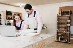 Jeune position heureuse de famille à un banc de travail dans un atelier de menuiserie, écrivant un projet Affaire de famille Jeun image libre de droits