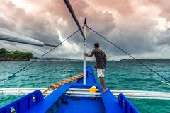 Jeune position philippine d'homme au bord du yacht regardant la mer Déplacement sur le vieux bateau au jour nuageux photos libres de droits