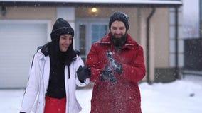 Jeune position positive de couples dans l'arrière-cour devant la grande maison sous la neige en baisse Homme barbu et clips vidéos