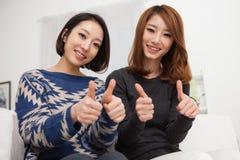 Jeune pouce asiatique d'exposition de la femme deux Image libre de droits