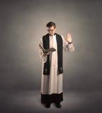 Jeune prêtre en donnant sa bénédiction photographie stock libre de droits