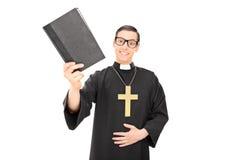 Jeune prêtre heureux tenant une Sainte Bible Photographie stock libre de droits