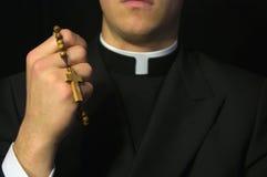 Jeune prêtre priant avec le rosaire Image libre de droits