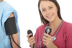 Jeune pression femelle décontractée professionnelle de docteur Taking The Blood d'un patient Photo libre de droits