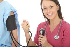 Jeune pression femelle professionnelle heureuse de docteur Taking The Blood d'un patient photo stock