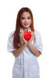 Jeune prise femelle asiatique de docteur un coeur et un sourire rouges Photos libres de droits