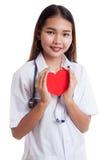 Jeune prise femelle asiatique de docteur un coeur et un sourire rouges Image libre de droits