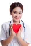 Jeune prise femelle asiatique de docteur un coeur et un sourire rouges Images libres de droits