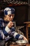 Jeune prisonnier féminin soufflant sur le thé chaud dans une tasse en aluminium dans a Photo libre de droits