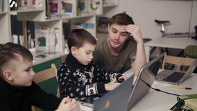 Jeune professeur attactive masculin dans son 20 ` s expliquant quelque chose à deux petits garçons, leur enseignant comment utili clips vidéos