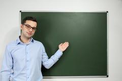Jeune professeur beau tenant le tableau noir proche Photos stock