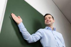 Jeune professeur beau tenant le tableau noir proche Photographie stock libre de droits
