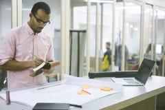 Jeune professeur et étudiant notant des idées dans l'organisateur personnel tout en créant le modèle graphique Photographie stock