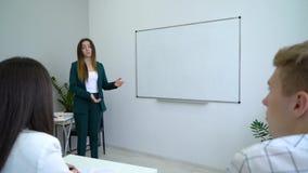 Jeune professeur heureux près des étudiants de enseignement de tableau blanc dans la salle de classe banque de vidéos