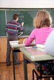 Jeune professeur mâle expliquant des maths au tableau noir Images stock