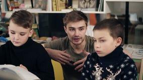 Jeune professeur masculin attirant avec des tatouages de couples sur ses bras expliquant quelque chose à deux petits garçons dans banque de vidéos