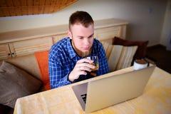 Jeune professionnel surfant l'Internet sur son ordinateur portable et buvant du whiskey d'un verre image libre de droits